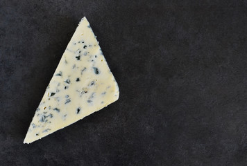 Slice of blue cheese on a black background