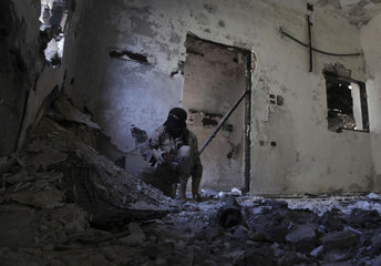 A Free Syrian Army fighter looks up as he takes up a position inside a damaged house in Deir al-Zor