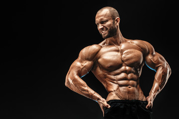 Strong bald bodybuilder with six pack. Strong bodybuilder man with perfect abs, shoulders,biceps, triceps and chest, personal fitness trainer flexing his muscles