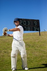 Cricket player swinging bat while standing at field