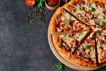 Home pizza with salami, tomato and cheese on a black background