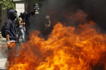 Demonstrators gather next to a barricade as they clash with riot policemen during a national strike in Santiago