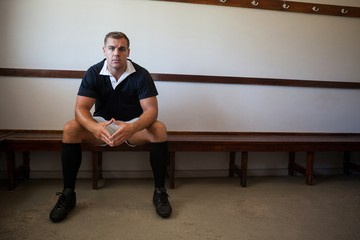 Portrait of confident rugby player sitting on bench