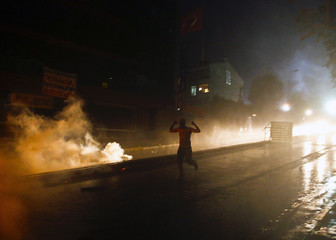 A protester runs for cover as police use water cannons and tear gas against a crowd of about 200 protesters in Istanbul's Gazi neighborhood