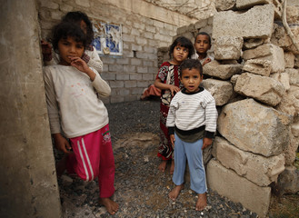 Children stand outside a house during a polio immunization campaign in an outskirt of the Yemeni capital Sanaa