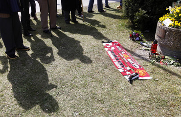 Manchester United supporters cast shadows next to memorial in Munich