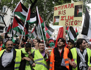Protesters wave flags and hold up banners during an anti-Israel demonstration in Vienna
