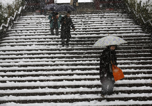 People walk down snow-covered stairs at a temple as snow falls in Tokyo
