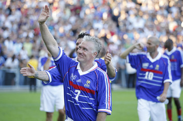 France 98's Deschamps waves to the fans after playing against a European selection during a charity soccer match in Nantes for the victims of flooding
