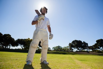 Confident player with cricket bat standing against sky