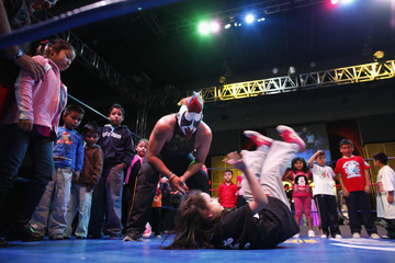 """Mexican lucha libre wrestler Murder Clown looks at a girl as she performs a stunt during a children's wrestling workshop at the sixth annual """"Lucha Libre: the Experience"""" expo in Mexico City"""