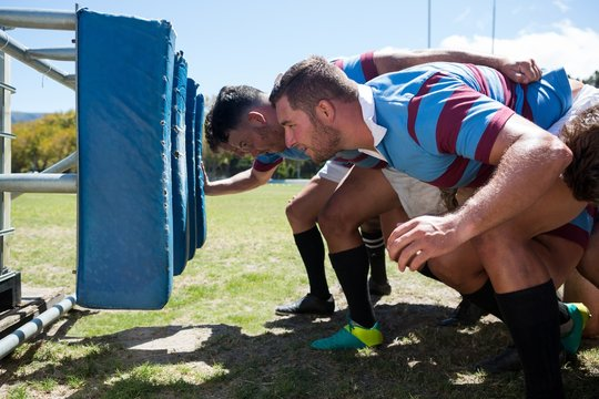 Side view of rugby players crouching at field