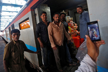 People pose for a picture with an idol of Hindu elephant god Ganesh, the deity of prosperity, on a train at a railway station in Mumbai