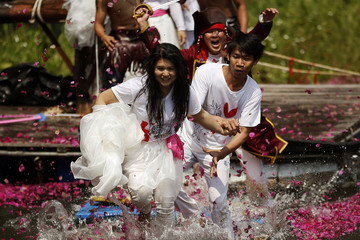 Groom and bride run as they are chassed by men dressed as pirates during a wedding ceremony ahead of Valentine's Day in Prachin Buri province