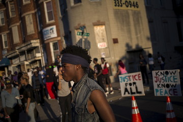Signs are seen in the background as a man takes part in a post-march street celebration in west Baltimore, Maryland