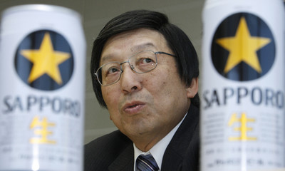 Sapporo Holdings Chief Executive Takao Murakami is seen through the company's Sapporo draft beer cans during an interview in Tokyo