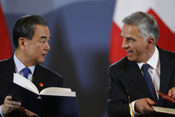 Chinese foreign minister Wang Yi and Swiss Federal Councillor and minister of Foreign Affairs Didier Burkhalter sign documents during an official visit in Bern