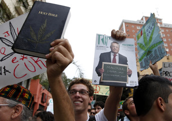 Demonstrators hold a Holy Bible with a drawing of a marijuana plant, and a picture of Brazil's former President Cardoso during a pro-marijuana legalisation march in Sao Paulo