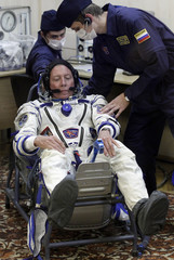 Russian Space Agency experts help U.S. astronaut Fossum to stand up after inspecting his spacesuit prior to the launch of the Soyuz TMA-02M rocket at the Baikonur cosmodrome
