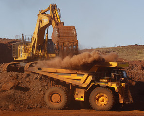 A trackhoe fills a dump truck in the South Limb pit at Atlas Iron's Pardoo mine