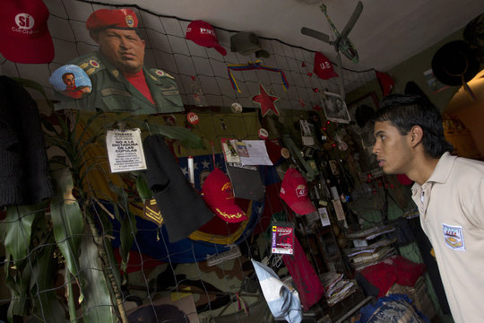 Teran looks at an image of Venezuela's President Chavez in the family collection of revolution-related items at his living room in Caracas