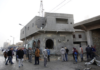 Residents gather at the site of a car bomb attack in the Hurriya District in Baghdad