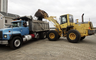 A front-end loader dumps a bucket load of sand scooped from Atlantic Avenue into a dump truck, following the aftermath of Hurricane Sandy in Atlantic City