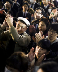 People listen to Japanese Prime Minister Abe speak ahead of upcoming election in Tokyo