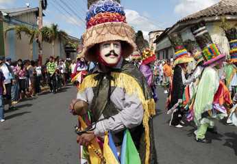 A parishioner, wearing a traditional mask and costume, dances during a feast in honour of Saint Sebastian, patron saint of Diriamba, in Diriamba