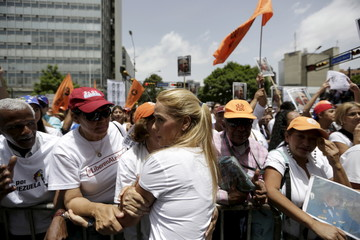 Lilian Tintori, wife of opposition leader Leopoldo Lopez, salutes opposition supporters during a demonstration in Caracas