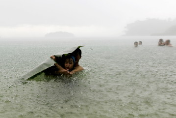 A young girl covers herself from the rain with a banana leaf next to a man in the sea on the outskirts of Colon City