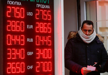 A man looks on next to a board showing currency exchange rates in Kiev