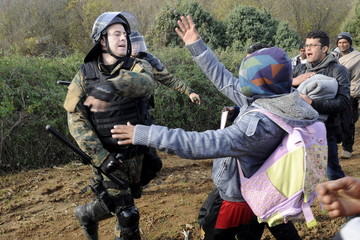 A Macedonian police officer hits a stranded migrant attempting to cross the Greek-Macedonian border, near Gevgelija
