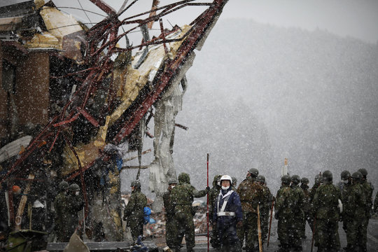 Heavy snow falls as members of the Japan Self-Defense Force arrive at the devastated residential area in Otsuchi