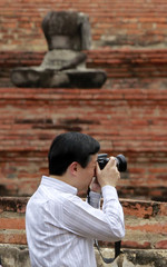 Japan's Crown Prince Naruhito takes a photograph as he visits the Wat Mahathat temple in Ayutthaya