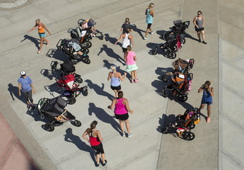 Young children sit watching from strollers as their mothers workout along the beach in Oceanside