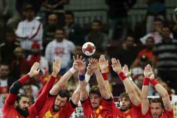 Spain's players attempt to block a shot of Mganem of Tunisia during the round of 16 match of the 24th men's handball World Championship in Doha
