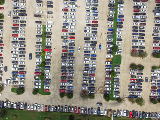 Aerial view full cars at large outdoor parking lots in Houston, Texas, USA. Outlet mall parking congestion and crowded parking lot with other cars try getting in and out, finding parking space.