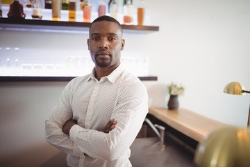 Man standing with arms crossed in restaurant