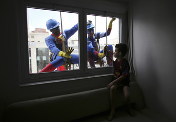Men dressed as Superman and Captain America smile at a patient at a children's hospital in Sao Paulo
