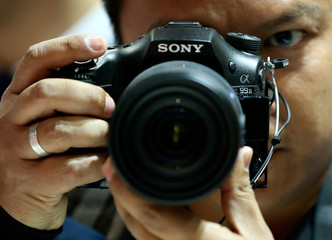 A visitor checks out the new Sony Alpha 99 Mark II DSLR camera at the Sony booth on the Photokina fair for imaging in Cologne