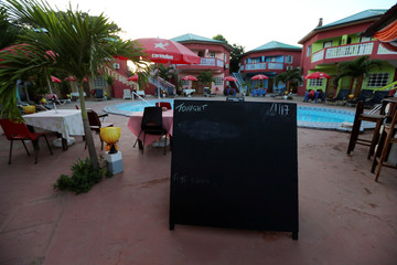 A chalkboard used to show the daily menu stands by the pool of a hotel in Banjul