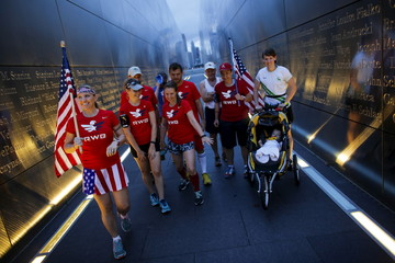 Members of the Red White and Blue team walk through the 9/11 Empty Sky memorial after posing for a picture at sunrise across from New York's Lower Manhattan and One World Trade Center, in Liberty State Park in Jersey City, New Jersey