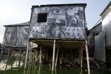 Photographs of garment workers taken by students of the Counter Foto photography department are seen covering stilt houses by the waterfront of Korail slum at Gulshan area in Dhaka
