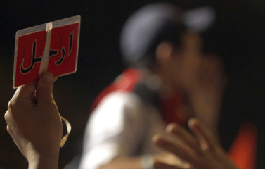 A protester, opposing Egyptian President Mohamed Mursi, holds up a soccer red card during Mursi's speech to the nation in Cairo