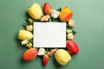 Beautiful flowers and green leaves as floral frame and paper card on color background