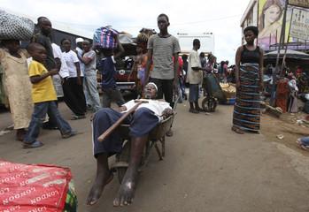 A man uses a wheelbarrow to transport his relative at Adjame in Abidjan