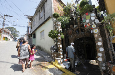 Residents walk past the home of Brazilian gardener Silva da Conceicao as he washes the front of his home which he calls the House of Stone in the Paraisopolis slum of Sao Paulo