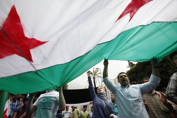 Protesters shout slogans and wave Syrian opposition flags during a demonstration, organised by Future party and Islamist Sunni group of al-Jamaat al-Islamiya, against Syria's President Bashar al-Assad after Friday prayers in Beirut