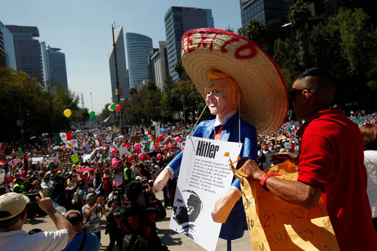 A man holds an effigy of U.S. President Donald Trump wearing a Mexican hat during a march to protest against Trump's proposed border wall and to call for unity, in Mexico City